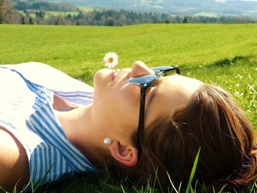 Chica en un prado sujetando una margarita con la boca y luciendo unas gafas de sol que la protegen de la radiación solar y ultravioleta tras su intervención de miopía.